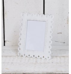 A small white metal photo frame with scalloped cut out edge