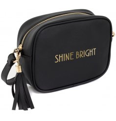 """A glamorously styled black faux leather side bag with a chic gold """"Shine Bright"""" quote"""