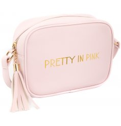 "A glamorously styled pink faux leather side bag with a chic gold ""Pretty in pink"" quote"