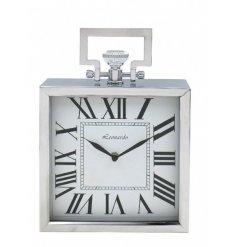 A small, square silver table clock