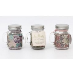These green, pink and purple wax candles in glass pots come in beautiful floral and butterfly inspired design,