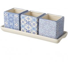 A chic set of 3 blue patterned ceramic planters on a white tray