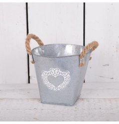 A large zinc bucket with white washed heart design
