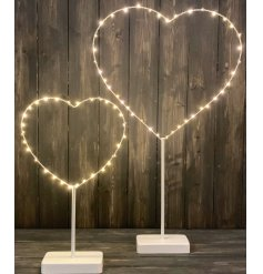 A rustic standing heart ornament wrapped with warm glow LED lights. A shabby chic table top item