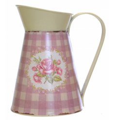 A cream and pink metal jug with gingham and rose pattern