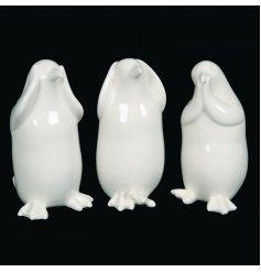 An assortment of 3 white ceramic penguins