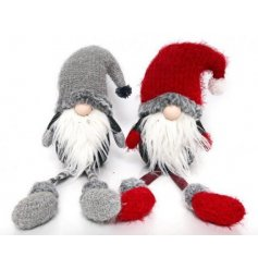 A mix of two red and grey adorable gonk shelf sitters with dangling legs. A cosy nordic style decoration.