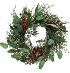 A decorative wreath built up with pine and fern foliage, topped with a light scatter of festive red berries