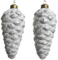 A sleek set of glass pinecones, set with a white lacquer finish