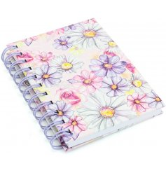 A beautifully illustrated notebook, detailed with a floral decal and purple spiral spine