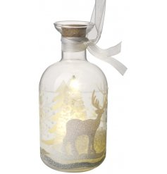 A beautifully decorated glass bottle decoration, set with a snowy tree centre and a warm glowing LED light