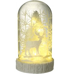 A beautifully decorated glass dome decoration, set with a snowy tree centre and a warm glowing LED light