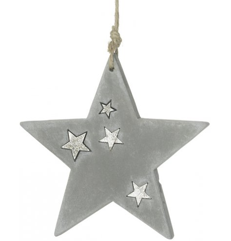 A concrete star decoration decorated with silver sparkling stars and hung with jute string ribbon.