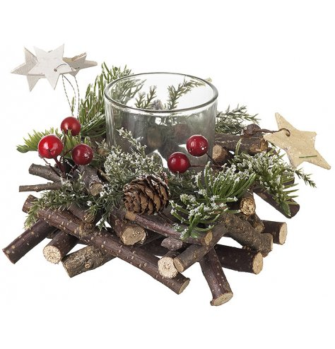 A hatched wooden twig wreath with red berries, glitter stars and pinecones surrounding a glass candle holder.