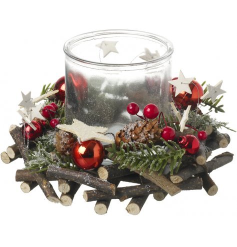A rustic twig wreath with Christmas red baubles, berries and stars surrounding a glass candle holder.