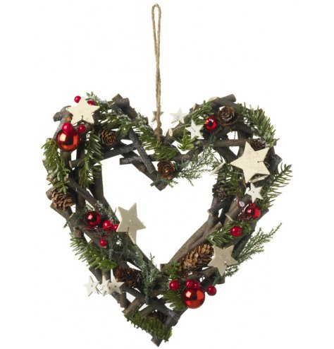 A rustic twig heart shaped wreath with artificial greenery, red berries, red baubles, pinecones and glitter stars.
