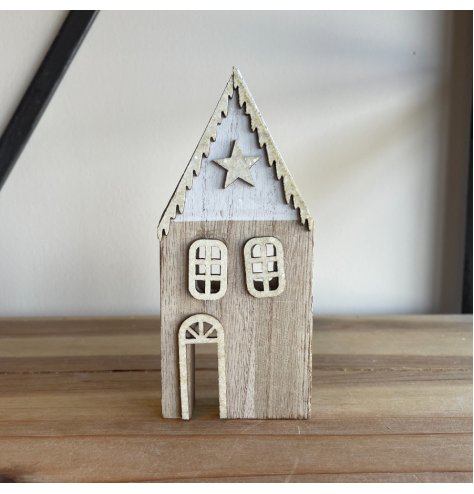A contemporary wooden house decoration with a silver snow topped roof and silver star embellishment.