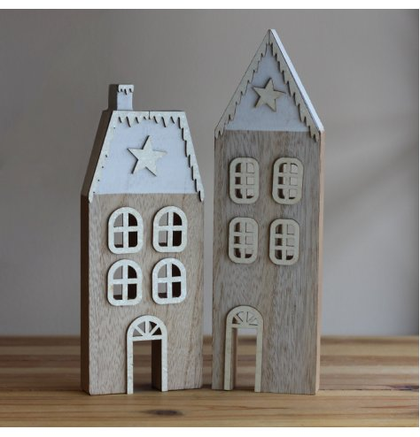 Stylish wooden houses with silver snow topped roofs, traditional windows and silver wooden stars.