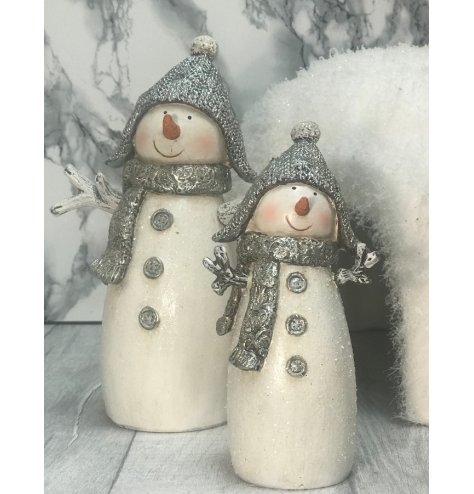 A beautifully detailed snowman figure with silver hat, scarf and buttons.