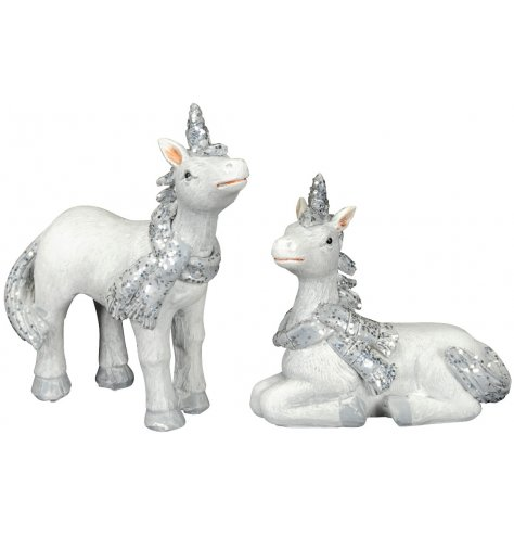 Standing and laying white and silver unicorn figures with glitter covered horn, tail, scarf and hooves.