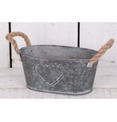 This oval zinc planter with embossed heart design and rope handles will add a touch of rustic romance to any home decor.