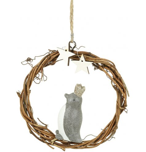 A rustic woven wreath adorned with white wooden stars and a royal penguin wearing a gold glitter crown.