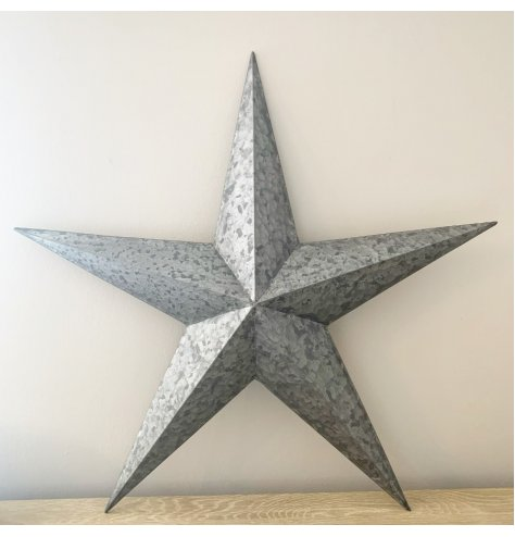 A large metal barn star with a hammered, distressed finish and 3-dimensional points.