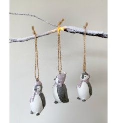 An adorable little trio of resin penguin figures each coated in a sprinkle of glittery snow