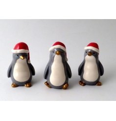 A mix of 3 unique penguin ornaments with gold feet and beaks. Each penguin is complete with a festive hat.