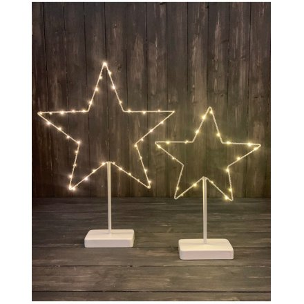 A stunning white metal star shaped standing decoration with warm glow LED lights.