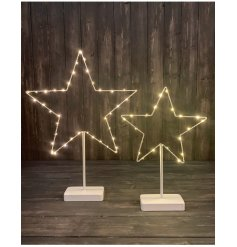 A stunning large shabby chic white standing star wrapped with warm glow LED lights.