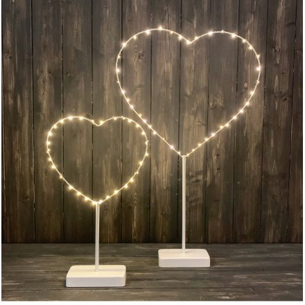 A rustic standing heart ornament wrapped with warm glow LED lights.