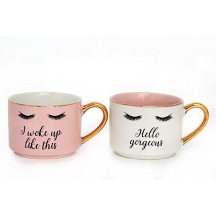 A mix of 2 glamorous mugs in pink and cream designs. Each has an eyelashes print and glamour slogan.