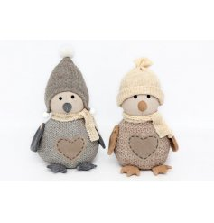An adorable assortment of sitting penguin doorstops, complete with their knitted winter outfits