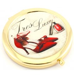 This stylish round golden compact mirror set with a red toned illustration and scripted 'Tres Luxe' print.