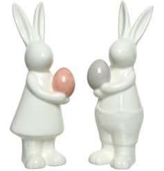 A charming assortment of white porcelain bunnies holding coloured eggs