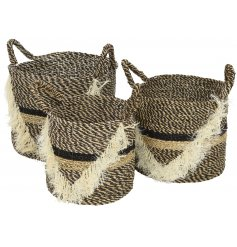 An assorted set of sized baskets with a black and natural tone pattern and added tasselled trim