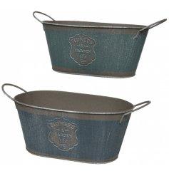 An assortment of 2 Flowers & Gardens rustic metal buckets with handles.