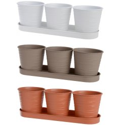 An assortment of 3 metal planters on matching trays, each set with an embossed line decal and matte colour