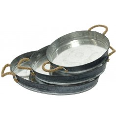 A set of 3 round zinc trays with a decorative motif and chunky rope handles.