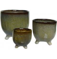 A set of 3 natural planters with feet. Each has an attractive blue and natural patterned glaze.