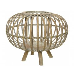 A hurricane lantern encased within a chic bamboo frame, placed on 4 feet.