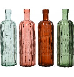 A mix of 4 tall coloured glass bottles with a wave and textured dot design.
