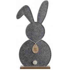 A chic large felt bunny on a wooden stand with an adorable pom pom tail and a wooden happy easter tag.