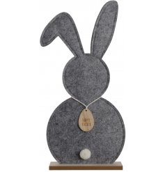 A chic grey felt bunny decoration on a wooden stand.