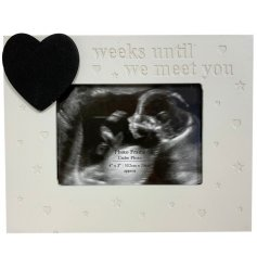 A neutral coloured baby scan photo frame with a heart shaped chalkboard to count down