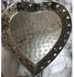 A rough finished and distressed silver set heart shaped plate, decorated with additional heart edges