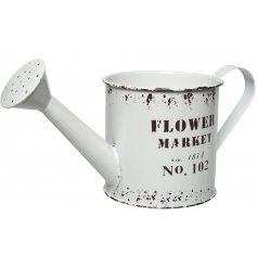 A rustic white metal watering can with a distressed Flower Market design. Ideal for planting and decoration.