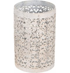 A shabby chic themed metal cut candle holder in a tall pillar form