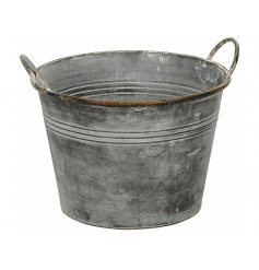 A charming rustic metal planter with a distressed finish and twin handles.